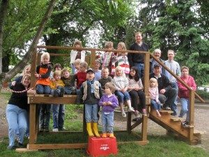 picture of children and parents outside on a play structure