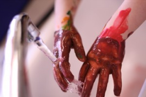 picture of a child washing paint off their hands