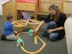 picture of a two year old playing with a train track